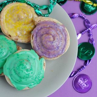 Everyone will love this Mini King Cake Recipe that is easy to make and full of color! The best part is, kids can help make this one. What is a Mini King Cake | What is a King Cake | How to Make a King Cake | How to Make Mini King Cakes