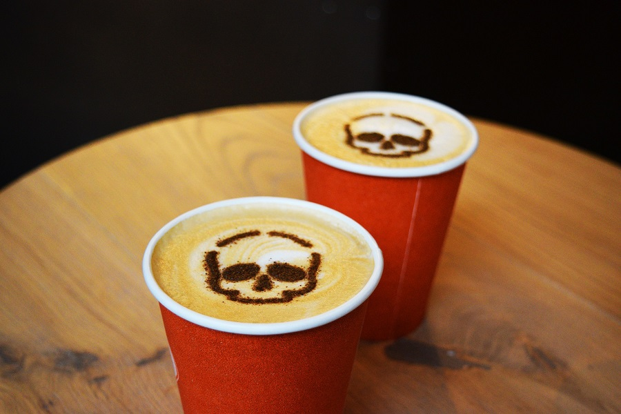 Pumpkin Drinks Two Cocktails Sitting on a Wooden Table with Skeleton Designs on the Top of Each Drink