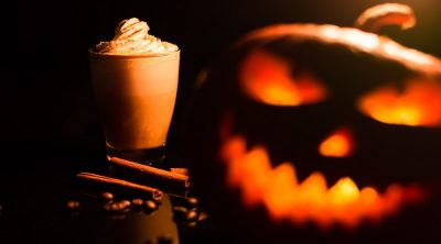 Pumpkin Drinks on a Blaco Surface with a Jack O Lantern in the Forefront
