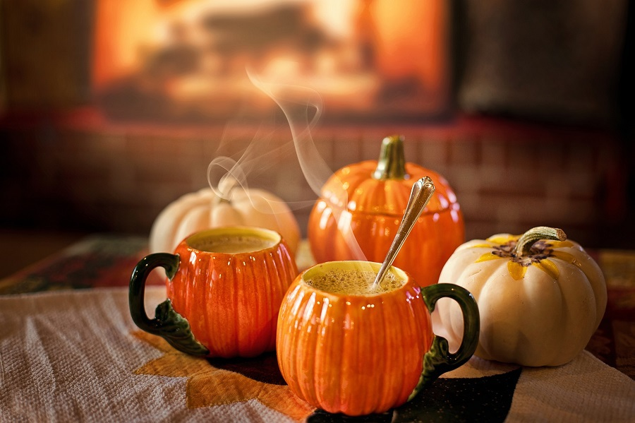Pumpkin Drinks Two Pumpkin Coffee Cups Sitting in Front of a Fireplace with Steam Coming From Each Cup