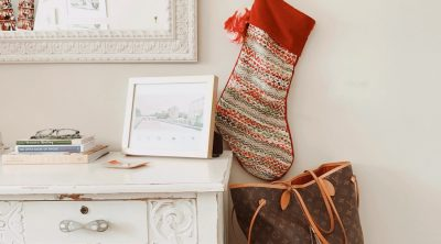 Stocking Stuffers for Women Stocking Hanging on a Wall Above a Purse Next to a Mirror