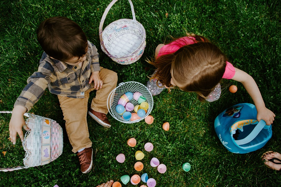 Easter Treats Two Kids Sitting on Grass Surrounded by Easter Eggs Holding Easter Baskets