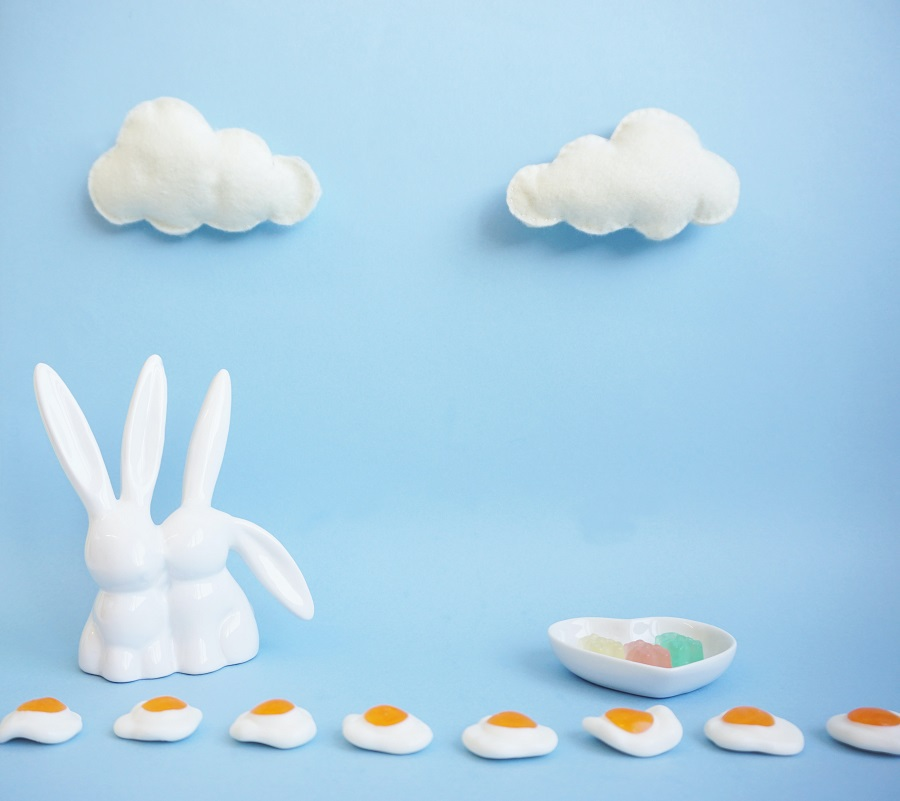 Easter Treats Glass Easter Bunny on a Blue Surface with Eggs Lined Up in Front