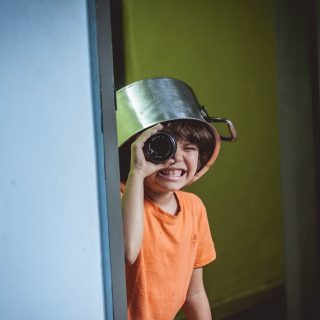 April Fools Prank Ideas for Friends Kid Wearing a Pot on His Head Holding a Camera Lens to One Eye As He Looks Around a Corner