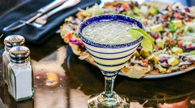 Cinco de Mayo Drinks Close Up of a Margarita with Nachos Behind Them