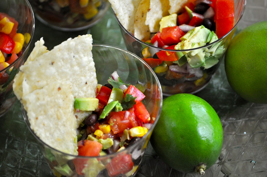 Black Bean Salsa in Plastic Cups with Limes Scattered Around