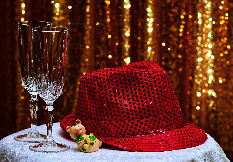 DIY New Years Decorations to Ring in the New Year a Red Hat with Champagne Flutes Next to it with a Golden Background
