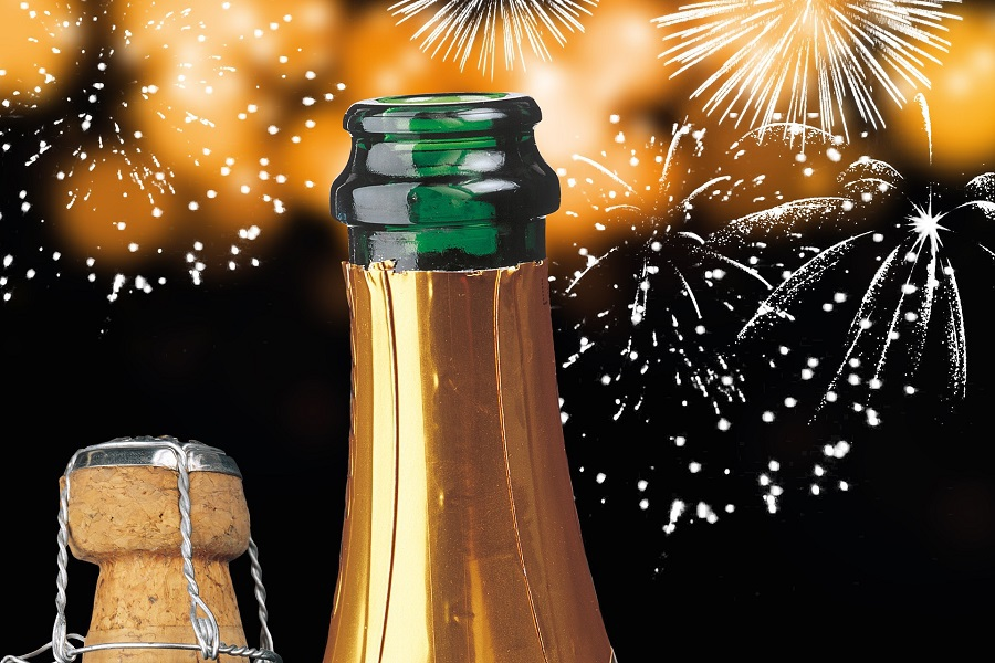 DIY New Years Decorations to Ring in the New Year Close Up of a Champagne Bottle with Fireworks in the Background