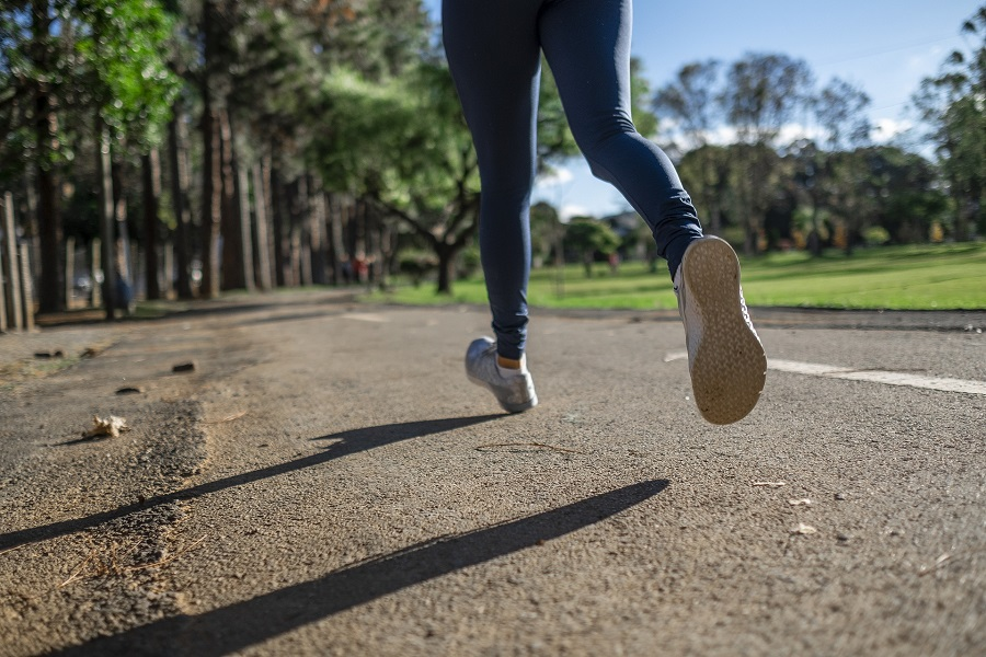 80 Day Obsession Close Up on Womans Legs as She Runs on a Paved Trail