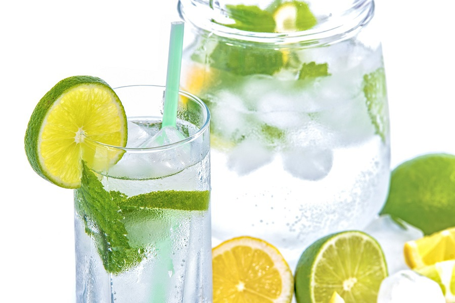 2B Mindset Recipes on Pinterest Close Up of a Glass of Water with a Lime Wedge on the Rim and a Pitcher in the Background Filled with Water