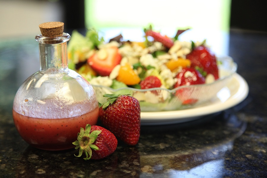 2B Mindset Recipes on Pinterest a Small Bottle of Red Salad Dressing Next to a Couple of Strawberries and a Salad in the Background