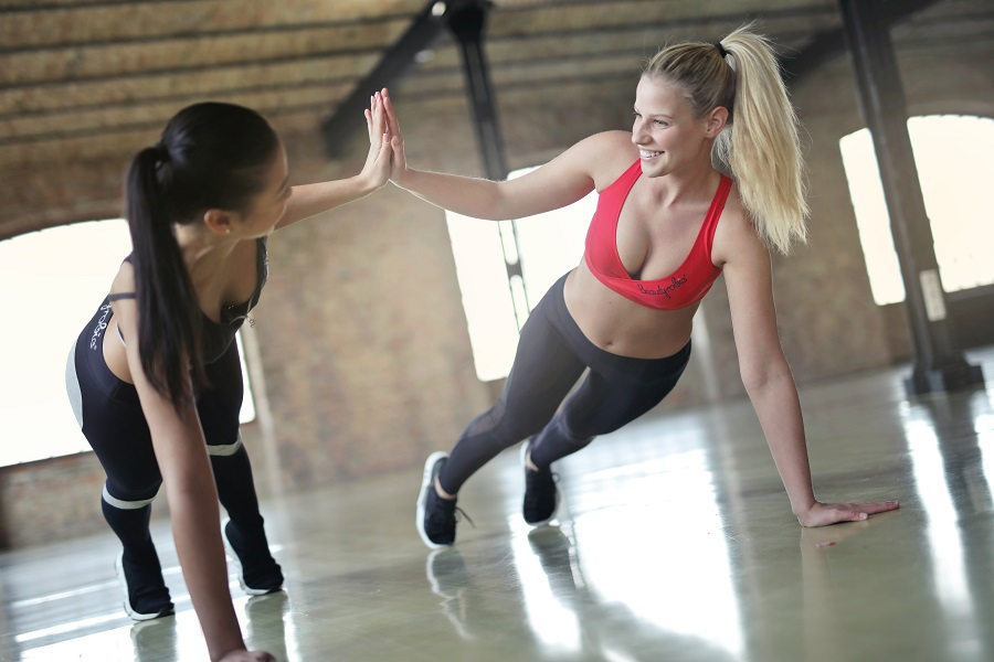 Oblique Workouts Two Women Doing Planks with One Hand as They High-Five