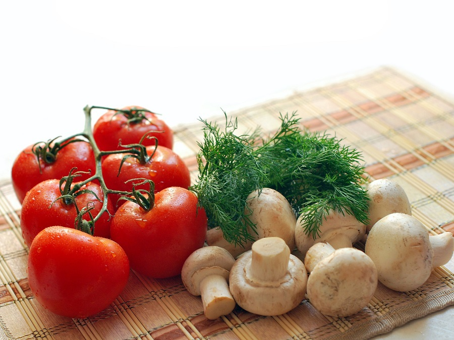 What Can You Eat on a Pegan Diet Close Up of Tomatoes, Mushrooms and Dill on a Cutting Board