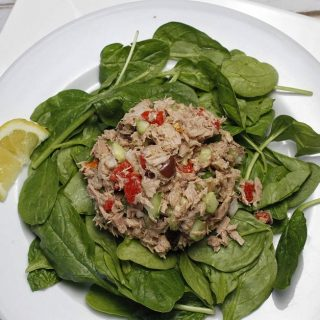 Overhead View of Mediterranean Tuna Salad on a Bed of Spinach.