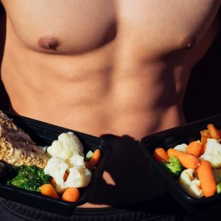 Low Carb Lunch Ideas Shirtless Man Holding To Plates of Healthy Food