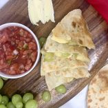 Brie and Grape Quesadilla Recipe Quesadilla Pieces on a Cutting Board with a Cup of Salsa Next to It
