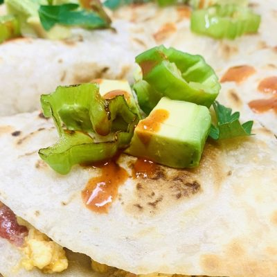 Healthy Breakfast Quesadilla Recipe Finished Quesadilla on a Cutting Board Close Up with Avocado
