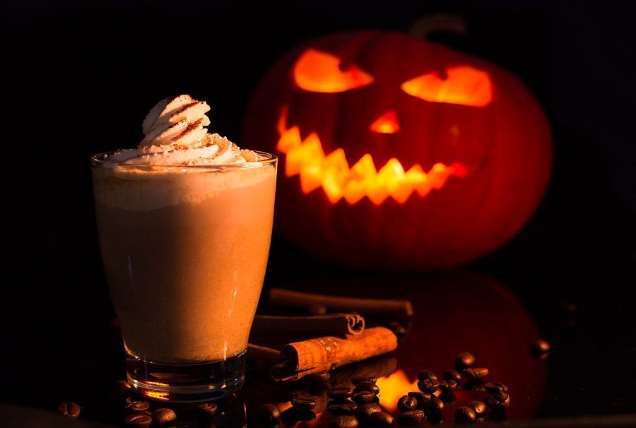 Halloween Crockpot Recipes Cup Filled with a Drink in Front of a Pumpkin