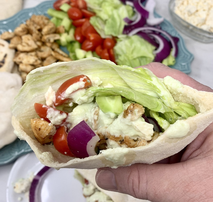 Chicken and Tzatziki in Pita Pockets Person Holding a Pita Pocket Above a Platter of Ingredients