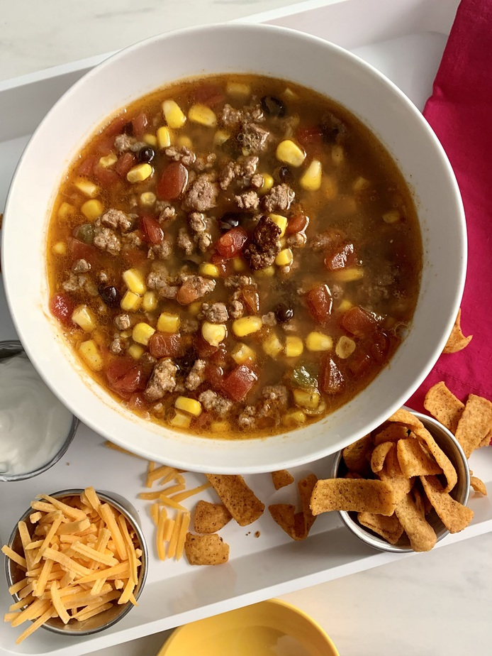 Crockpot Taco Soup Recipe Overhead View of a Bowl of Soup with Garnishes Surrounding The Bowl